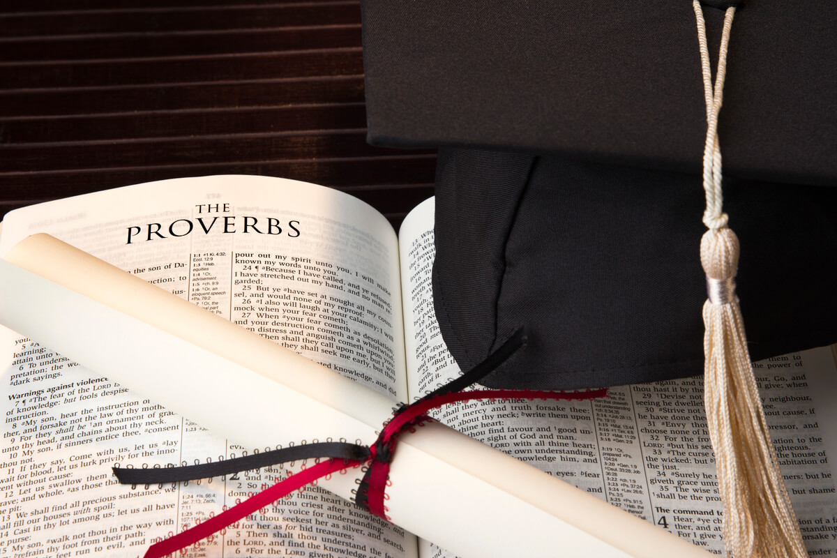 grad cap and diploma on top of a Bible