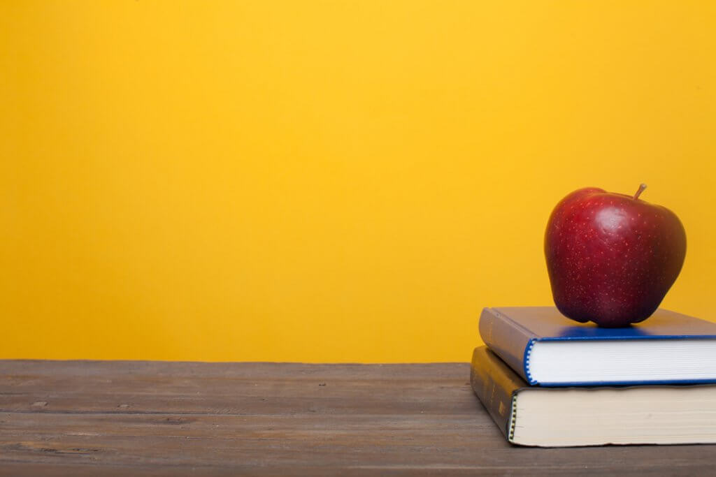 books on a table with an apple on top and yellow background