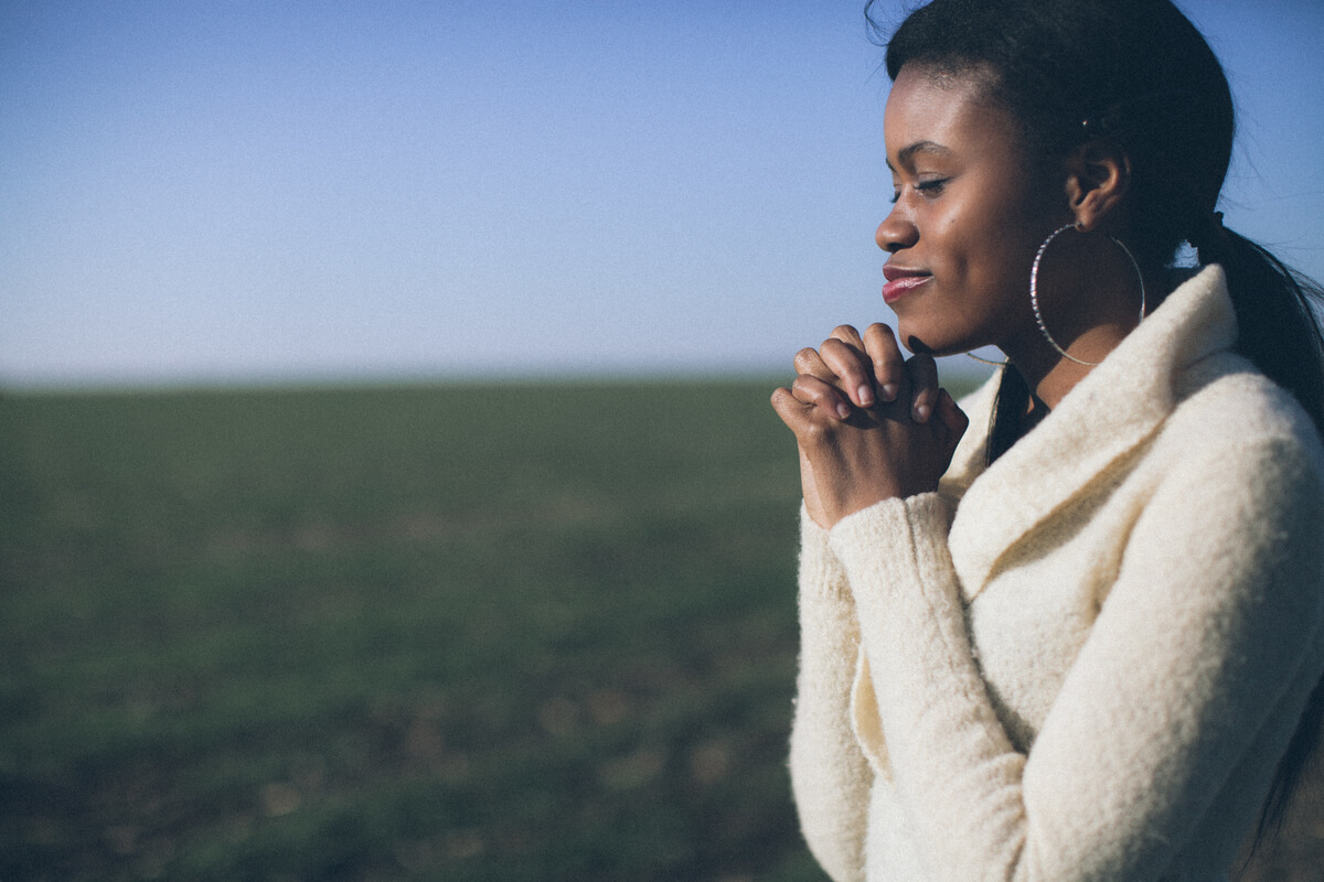Woman standing outside with hands folded in prayer