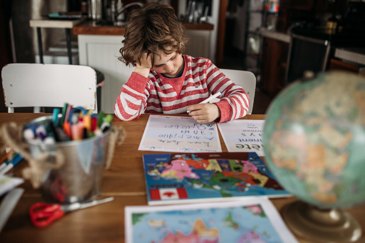 Boy doing schoolwork at table