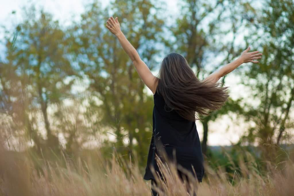 Woman standing in field with arms raised in worship