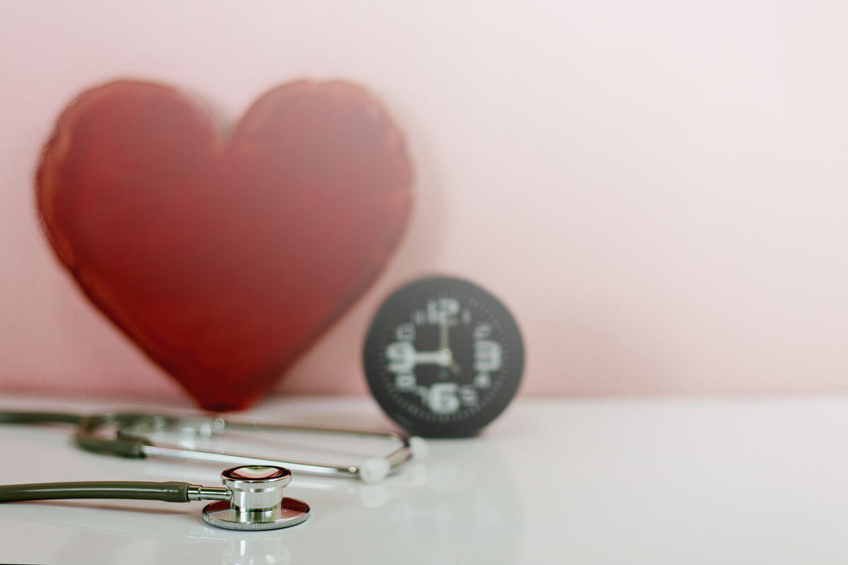 stethoscope lying on a table with a red heart propped against a wall behind it