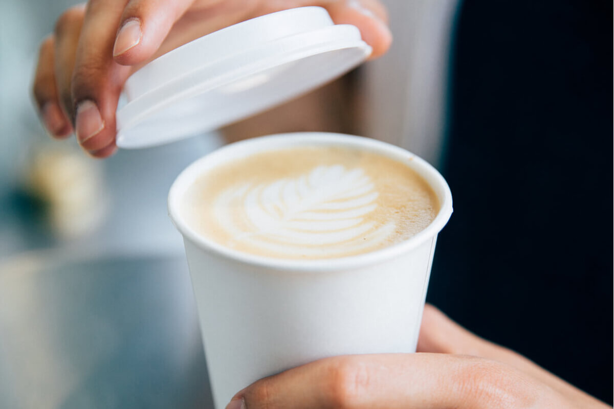 Putting lid on cup of coffee