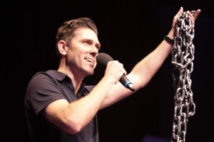 Man holding chains in left hand and microphone in right hand speaking