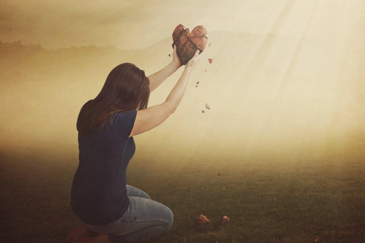 Woman on knees holding broken heart in sunlight