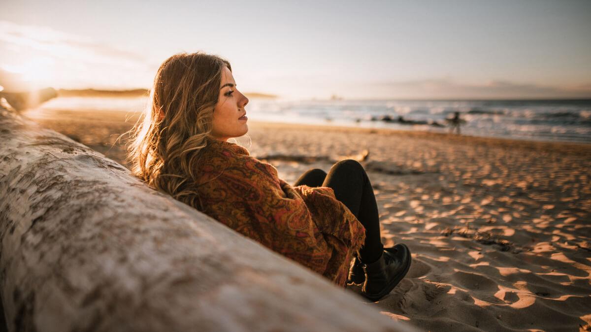 Woman sitting next to a log on a beach
