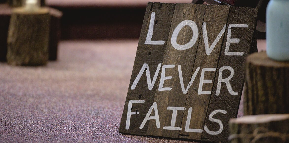Love never fails on a wooden sign