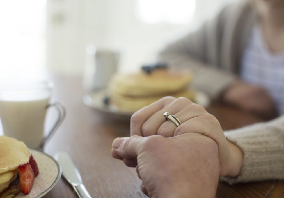 married couple holding hands breakfast